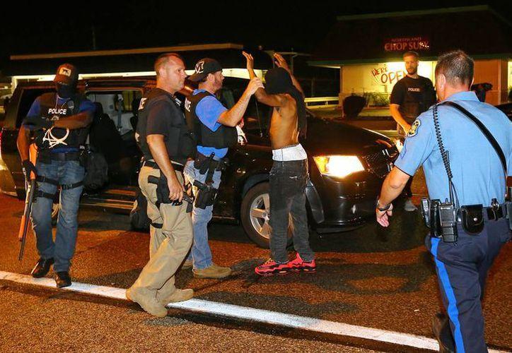 Un manifestante es arrestado mientras caminaba por la calle en West Florissant Avenue en Ferguson, Misuri. (Agencias)