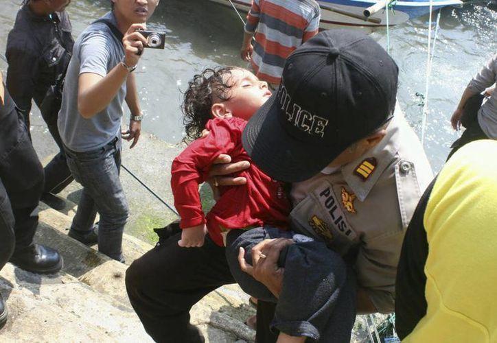 Un policía indonesio lleva en brazos a un niño exhausto, durante una operación de rescate en Cidaun, en la isla indonesia de Java. (EFE)