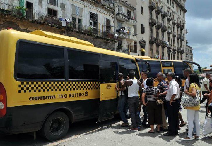 Varias personas hacen fila para subir a un ómnibus de una cooperativa de taxis colectivos  en La Habana. (EFE)