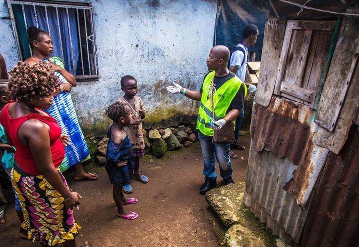 Un trabajado voluntario (con guantes en las manos) explica a los habitantes de Sierra Leona las medidas higiénicas para evitar el contagio del ébola, enfermedad que ha matado a más de 2,000 personas en África. (AP)