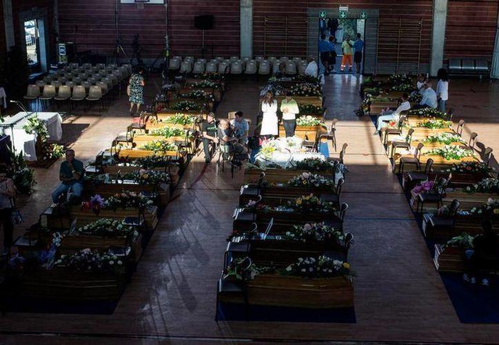 Los 35 ataúdes de víctimas del sismo en Italia se colocaron en el piso de un complejo deportivo, en Ascoli Piceno. (Notimex)