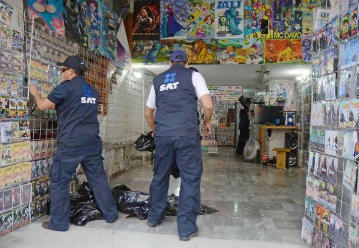 """Los agentes del SAT al momento de decomisar películas """"pirata"""" en un local en el Centro Histórico de Mérida. (Milenio Novedades)"""