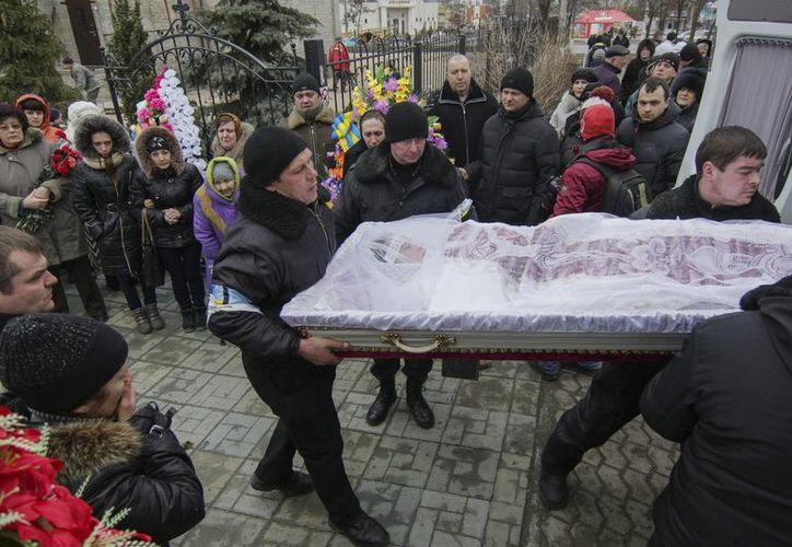 Varias personas asisten al entierro de Olga Abdurashitova, de 27 años, fallecida en el ataque con artillería en Mariúpol, Ucrania. (EFE)