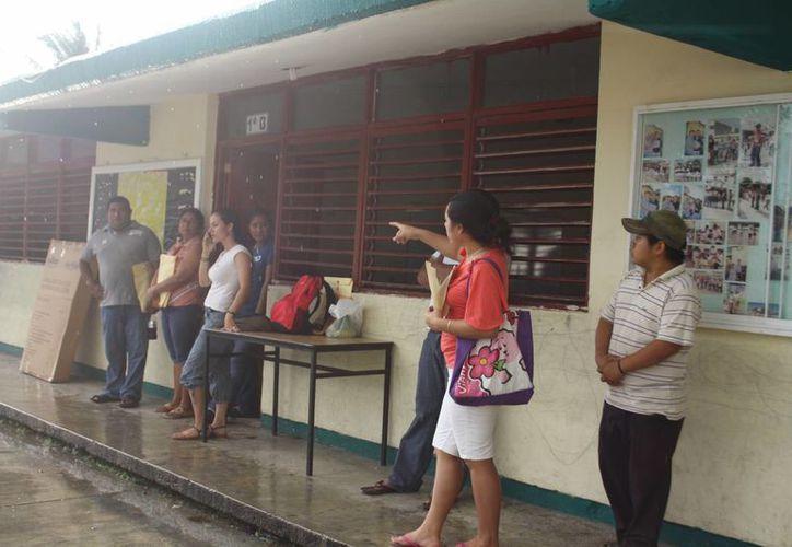 A pesar de la lluvia, algunos ciudadanos empiezan a formarse en espera de la apertura de casilla para emitir de manera puntual su voto. (Rossy López/SIPSE)