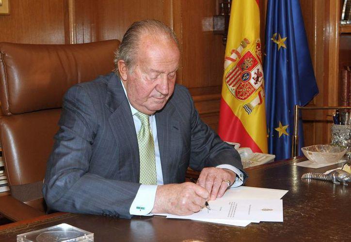 El Rey Don Juan Carlos, tras firmar el documento de su abdicación que, posteriormente, entregó al presidente del Gobierno, Mariano Rajoy. (EFE/Casa de S. M. el Rey)