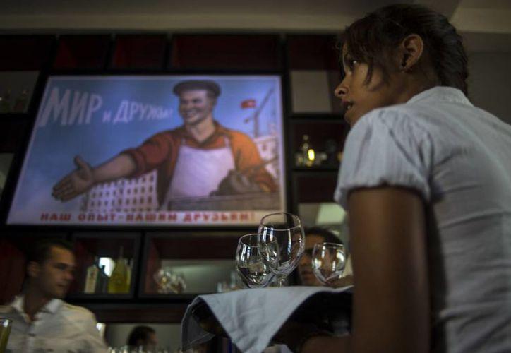 Fotografía que muestra a una mesera trabajando durante un ensayo previo a la inauguración del nuevo restaurante Nazdarovie en La Habana, Cuba. (Agencias)