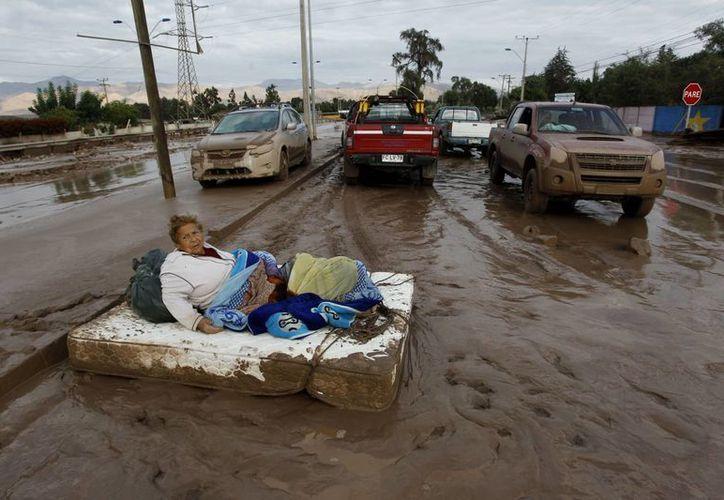 Una mujer descansa en un colchón rodeado de barro después de las inundaciones en Copiapó, Chile. (Agencias)