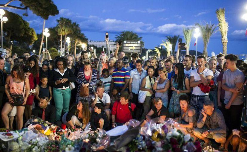Personas reunidas en un sitio improvisado en memoria de las víctimas cerca del sitio donde un camión arrolló a decenas de personas en Niza, Francia. (Agencias)