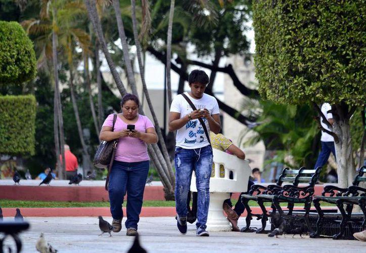 La llegada de la red compartida ayudará a mejorar la calidad del servicio de internet que se presta en Yucatán y el resto del país. Imagen de un par de jovenes mientras miran el celular, en la Plaza Grande, en el centro de Mérida. (Milenio Novedades)