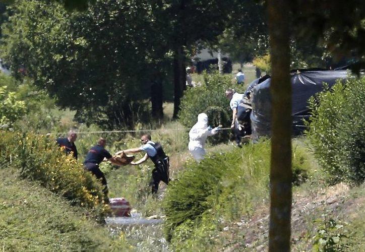 Imagen de los investigadores policiales que trabajan, hoy viernes, cerca de la planta en Saint-Quentin-Fallavier, sureste de Francia. Una fábrica de gas fue atacada y provocó una explosión. En el lugar se halló el cuerpo decapitado de un empresario local. (AP Photo/Laurent Cipriani)