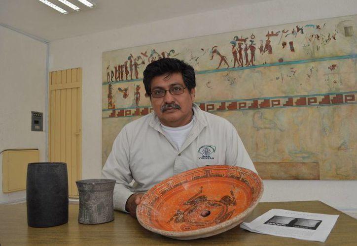 Un especialista del INAH Yucatán muestra una vasija encontrada en el complejo funerario maya en Mérida. (Notimex)