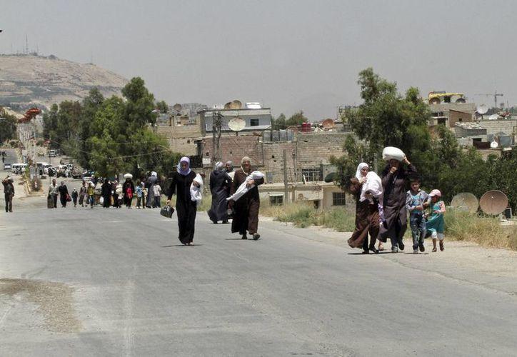 Sirios son captados al momento de regresar a Damasco, después conseguir alimentos. (Agencias)