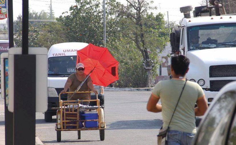 Conagua advierte de golpes de calor por la fuerte radiación solar y recomienda evitar salir a la calle sin gorras o sombrillas. (Juan Albornoaz/SIPSE)