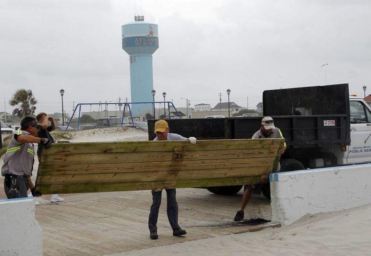 Trabajadores de la ciudad cierran un acceso a la playa en Atlantic Beach, NC, en previsión de la llegada del huracán Arthur. (AP Photo/The News & Observer, Chris Seward)