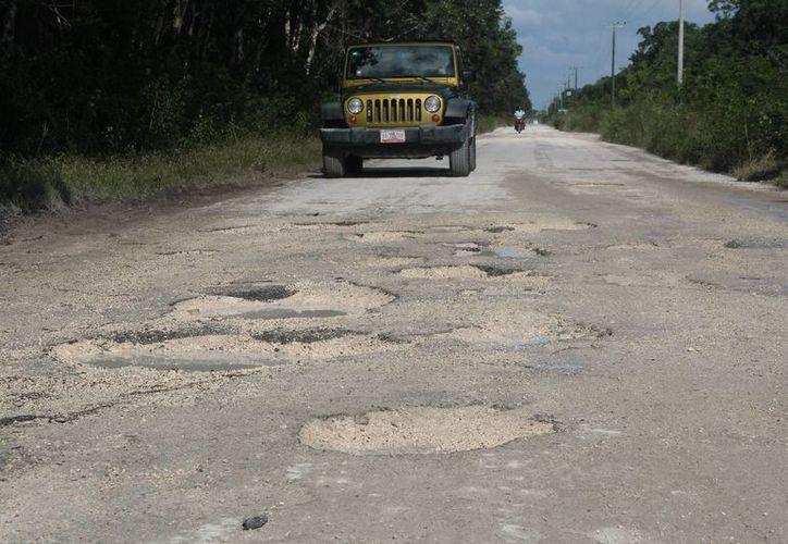 La carretera tiene baches en diversos tramos que dificultan el tránsito de vehículos. (Julián Miranda/SIPSE)