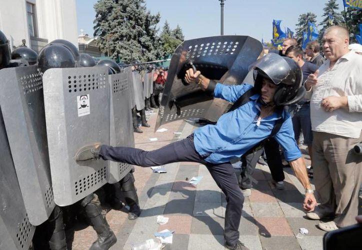 Manifestantes ucranianos se enfrentaron a agentes policíacos tras una votación de los legisladores para ceder mayor poder al este del país, este lunes en Kiev. (AP)