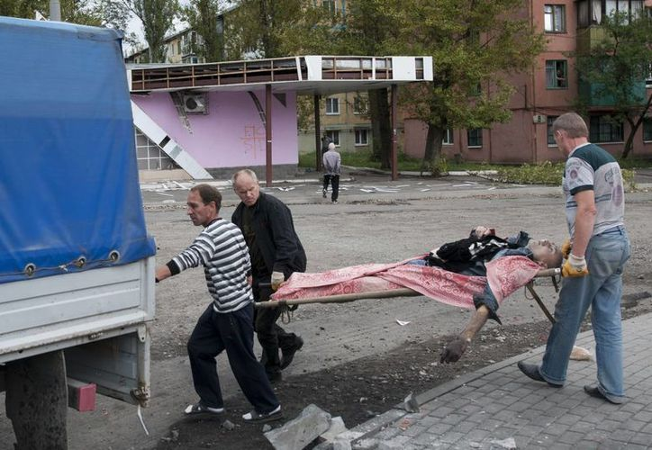 Personas trasladan en una camilla el cadáver de una víctima del cañoneo ucraniano en Makiivka, a 25 kilómetros de Donetsk, este de Ucrania. (Agencias)
