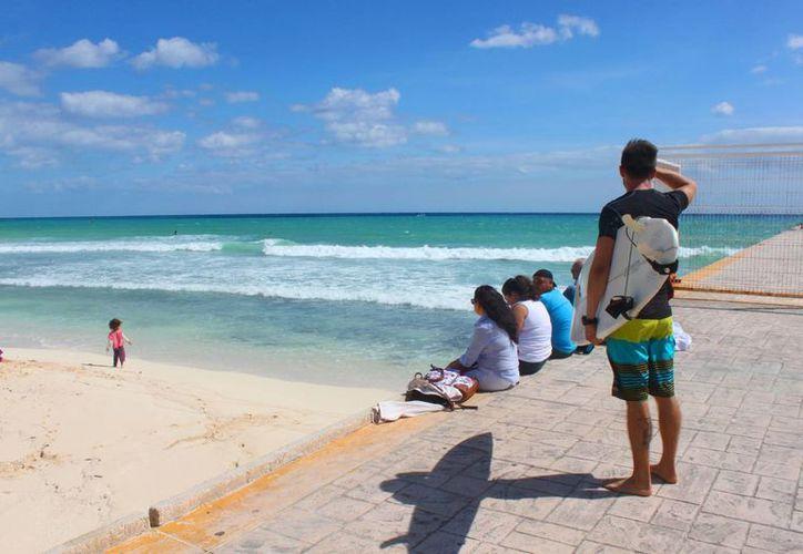 Desde el sábado en las playas del destino empezaron a aparecer grupos de surfistas, quienes con tabla en mano se adentraron al mar para practicar. (Daniel Pacheco/SIPSE)