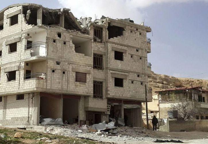 Soldados sirios pasan por delante de un edificio en ruinas en la localidad de Yarboud, a las afueras de Damasco. (EFE)