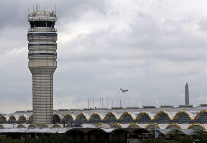 Un avión pasa frente a la torre de control aéreo en el aeropuerto Ronald Reagan en Washington el 10 de agosto del 2015. Un estudio de la NASA reveló que los controladores aéreos sufren de fatiga que pone en riesgo su labor. (Foto AP/Jacquelyn Martin)