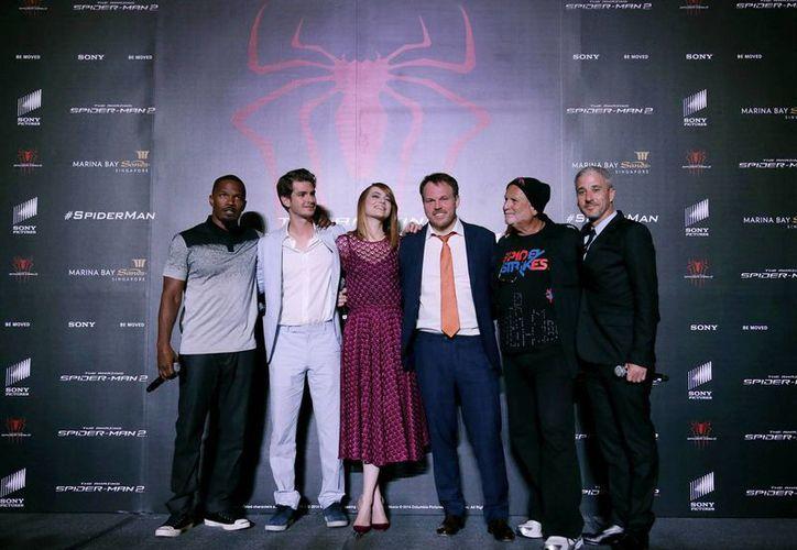 """Posando para la foto de izquierda a derecha, los actores Jamie Foxx, Andrew Garfield, Emma Stone, el director Marc Webb y los productores Avi Arad y Matt Tolmach al asistir a la alfombra roja de """"The Amazing Spider-man 2"""" en Singapur. (Agencias)"""