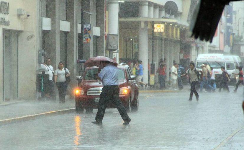 La lluvia sorprendió a muchos transeúntes en la calle. (José Acosta/SIPSE)
