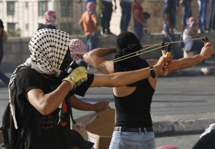 Muchachos palestinos usan resorteras en un enfrentamiento con tropas israelíes en la parte poeste de la ciudad de Belén, el miércoles 14 de octubre de 2015. (Foto: AP/Nasser Shiyoukhi)