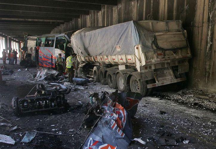 Policías y operarios observan el lugar donde chocaron un autobús y un camión. (EFE)