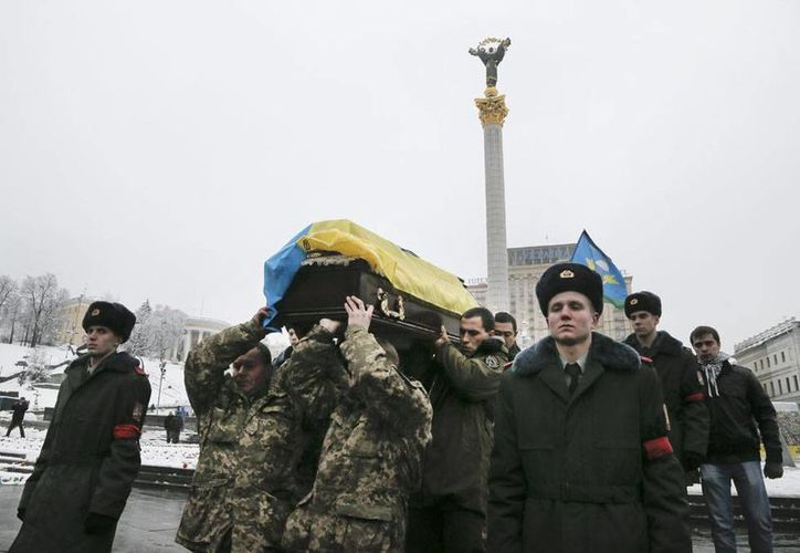 Soldados ucranianos cargan el féretro de un funcionario que murió durante enfrentamientos entre Ejército y rebeldes prorrusos, conflicto que hoy también dejó varios civiles muertos. (AP)