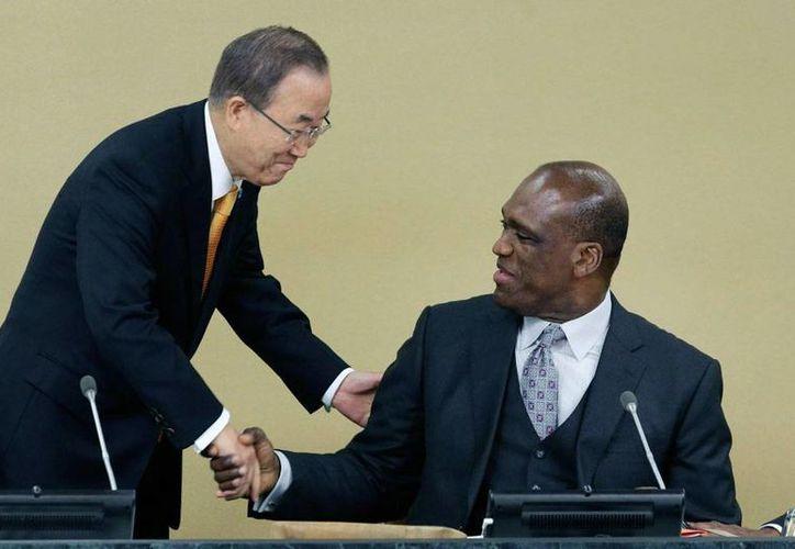 John Ashe (der.), ex presidente de la Asamblea General de la ONU, fue acusado de fraude. En la imagen, de archivo, saluda al secretario general de la organización, Ban Ki-moon. (AP)