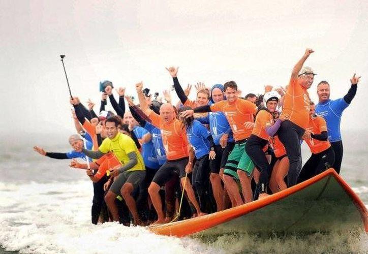 Sesenta y seis personas establecieron el sábado un récord mundial al mayor número de personas subidas al mismo tiempo a una tabla de surf. (AP)
