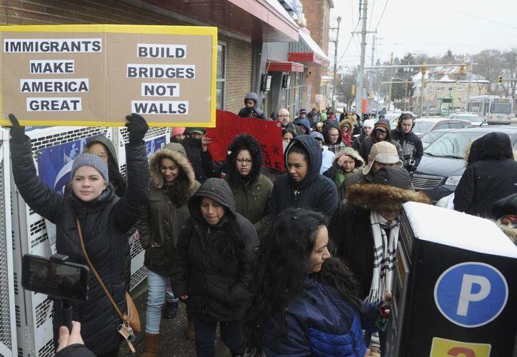 Varias decenas de residentes de la zona marcharon por la Avenida Broadway en la Avenida Beechview de Pittsburgh, este jueves, en protesta por las recientes medidas de represión contra los inmigrantes ordenadas por el presidente Donald Trump. (Nate Guidry / Pittsburgh Post-Gaceta vía AP)