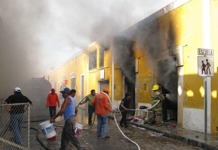 """Los bomberos batallaron para extinguir las llamas en """"La Tienda de la Abuela"""". (Milenio Novedades)"""