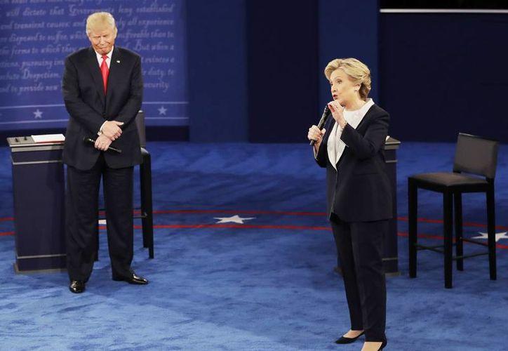 El candidato presidencial republicano Donald Trump escucha a la candidata demócrata Hillary Clinton durante el segundo debate presidencial en la Universidad de Washington en St. Louis, el domingo, 9 de octubre del 2016. (Foto AP / Patrick Semansky)