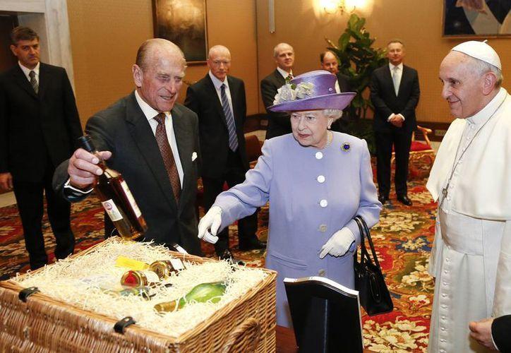 La Reina Isabel II de Inglaterra y su marido, el príncipe Felipe, intercambian regalos con el Papa Francisco. (Agencias)
