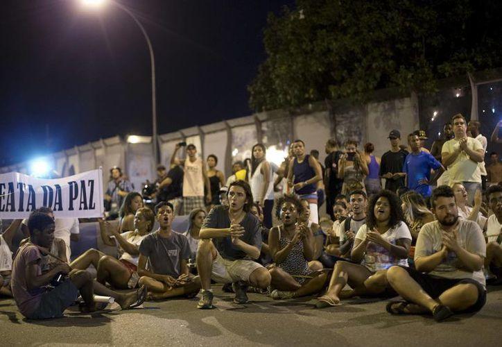 Civiles bloquean una avenida en Río de Janeiro, en protesta contra la violencia, la cual podría afectar los Juegos Olímpicos en esa ciudad en 2016. (Foto: AP)