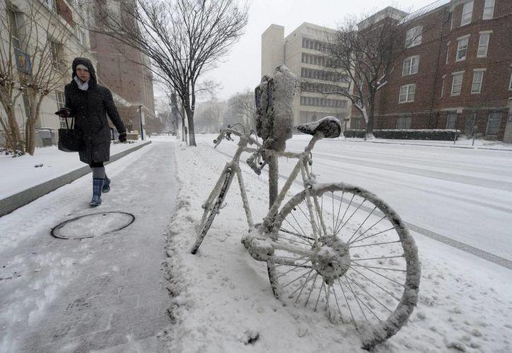 Una mujer camina junto a una bicicleta congelada durante la tormenta invernal de nieve en Washington, EU. (EFE)
