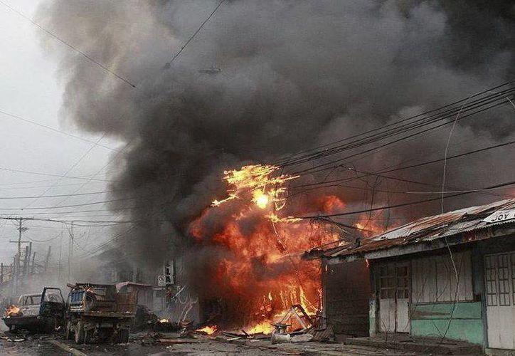 Una funeraria en llamas tras la explosión de un artefacto casero en la Avenida Sinsuat de Cotabato, Filipinas hoy. (EFE)