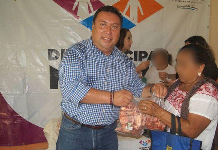 El editl Vicente Euán Andueza entregando uno de los 100 paquetes de huesitos. (Ayuntamiento de Motul/Facebook)