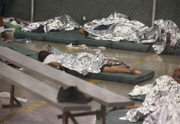 La mayoría de los menores detenidos duermen en pequeñas colcholetas con mantas que parecen papel aluminio. (AP)
