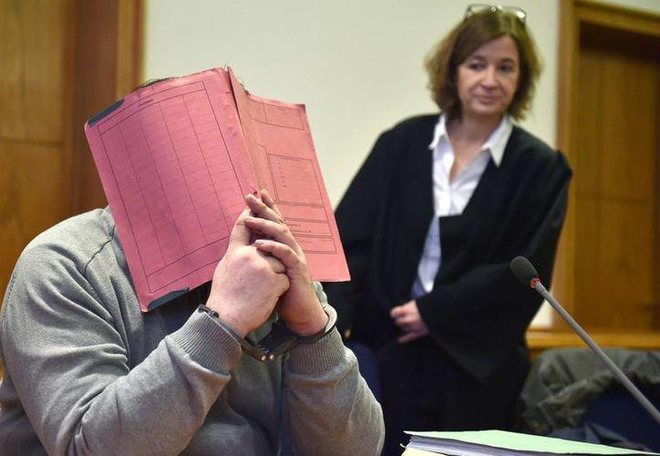 El exenfermero Niels H. se cubre el rosto mientras permanece en el banquillo de los acusados en el tribunal de distrito de Olenburg, Alemania. (Agencias)