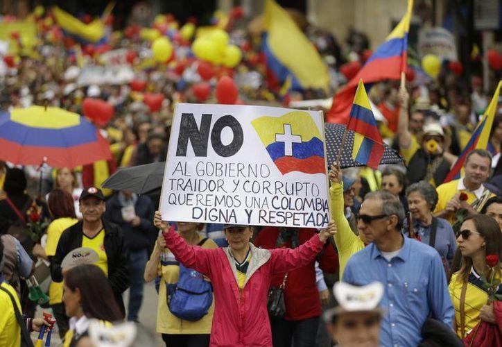 Hombres y mujeres de todas las edades, en 20 ciudades colombianas, vistieron camisetas amarillas y rojas y portaron pancartas que expresaban rechazo a las políticas presidenciales oficialistas de seguridad, empleo, salud y educación. La foto corresponde a Bogotá. (AP)
