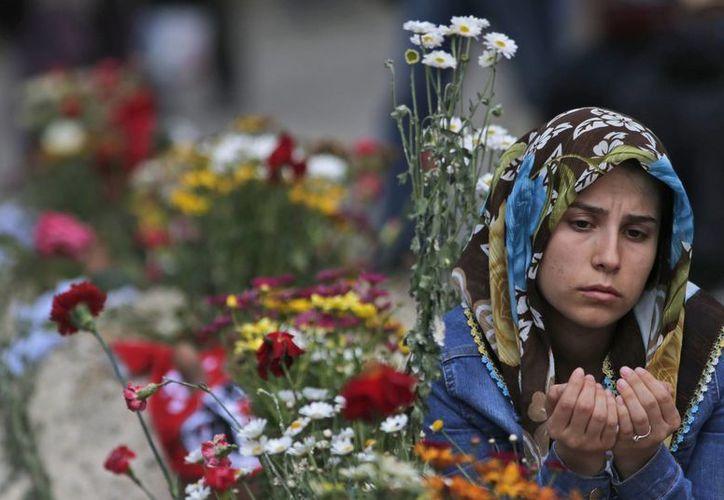 Un familiar de una víctima del accidente de la mina ofrece sus oraciones junto a la tumba de su ser querido, en Soma, Turquía. (Agencias)