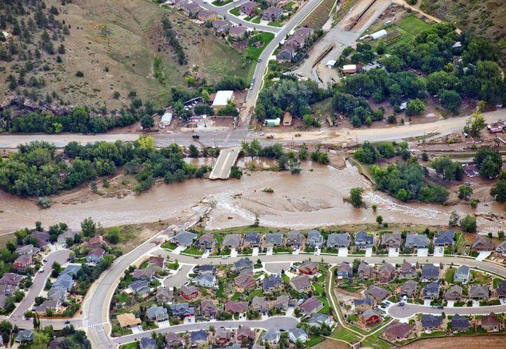 Los deslaves e inundaciones 'partieron' en dos un vecindario y unas vías de comunicacion en Lyons. (Agencias)