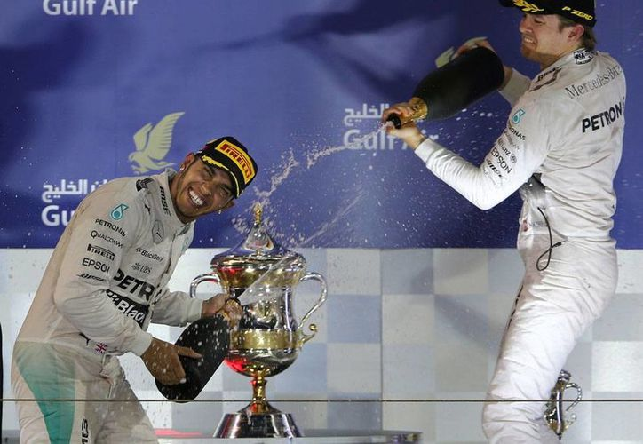 Lewis Hamilton (der.) celebra su triunfo con Nico Rosberg, tras el Gran Premio de Bahrein. (AP)