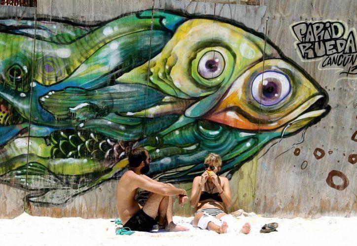 Los grafitis en muros de las playas de la localidad han resultado un atractivo para los turistas. (Adrián Monroy/SIPSE)