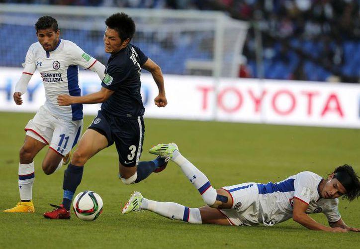 Cruz Azul nunca encontró la fórmula para vencer al Auckland City en partido del Mundial de Clubes. En la foto, el celeste Joao Rojas disputa la redonda con Takuya Iwata.  (Foto: AP)