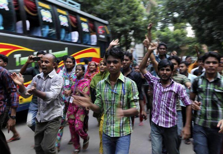 Trabajadores gritan consignas en Dhaka por sus deplorables condiciones de trabajo. (EFE)