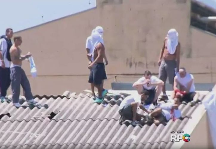 Imágenes de televisión muestran a los reclusos en la prisión del estado de Paraná en Londrina trepando por los techos y arrastrando a varios rehenes maniatados. (Captura de pantalla tomada de g1.globo.com)