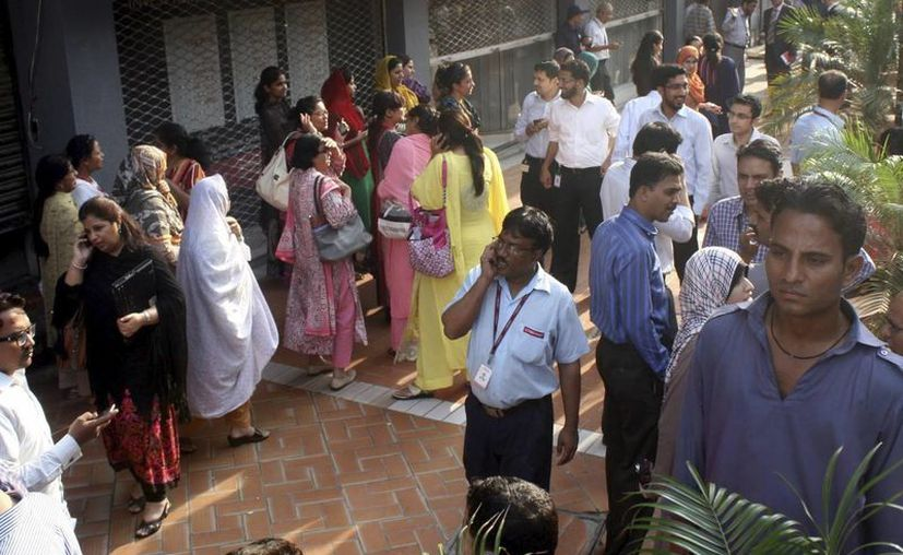 Varios trabajadores son evacuados en Karachi, Pakistán. (EFE)